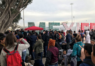 """Families wait at """"El Chaparral,"""" a border crossing near San Ysidro, California, to hear which names are called from the asylum waitlist. (Shannon Dooling/WBUR)"""