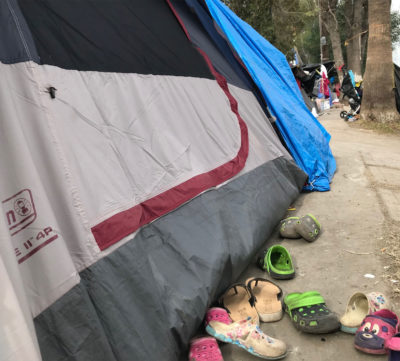 Shoes are lined up outside a tent near the Benito Juárez soccer stadium in Tijuana. There are an estimated 500 people, mostly from Central America, living in tents. (Shannon Dooling/WBUR)