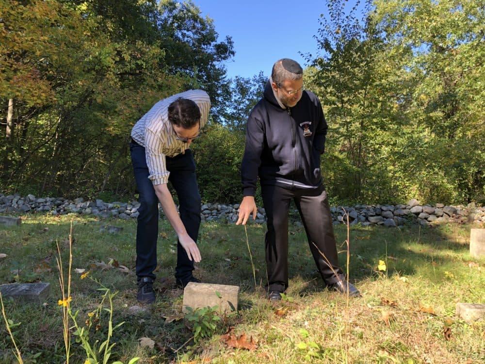 Historian Alex Green, left, and Gann Academy teacher Yoni Cadden point to a grave marker in Waltham's Metfern Cemetery (Eve Zuckoff/WBUR).