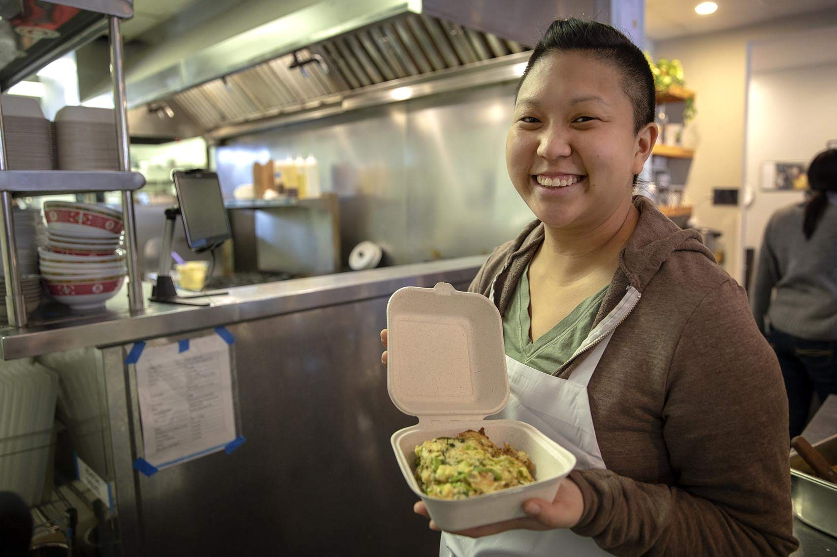 Mei Mei's Irene Li holds up a savory bread pudding she made from odds and ends found in her Boston restaurant's refrigerator. (Robin Lubbock/WBUR)