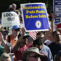 Protesters display placards during a rally July 18 in front of the State House, in Boston, held to call attention to the lockout of natural gas workers from their jobs by National Grid in dozens of communities across the state. (Steven Senne/AP)