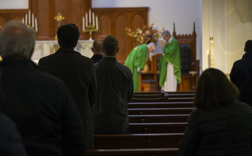 Parishioners stand in pews at Shrine of Our Lady of Good Voyage in the Seaport. (Jesse Costa/WBUR)