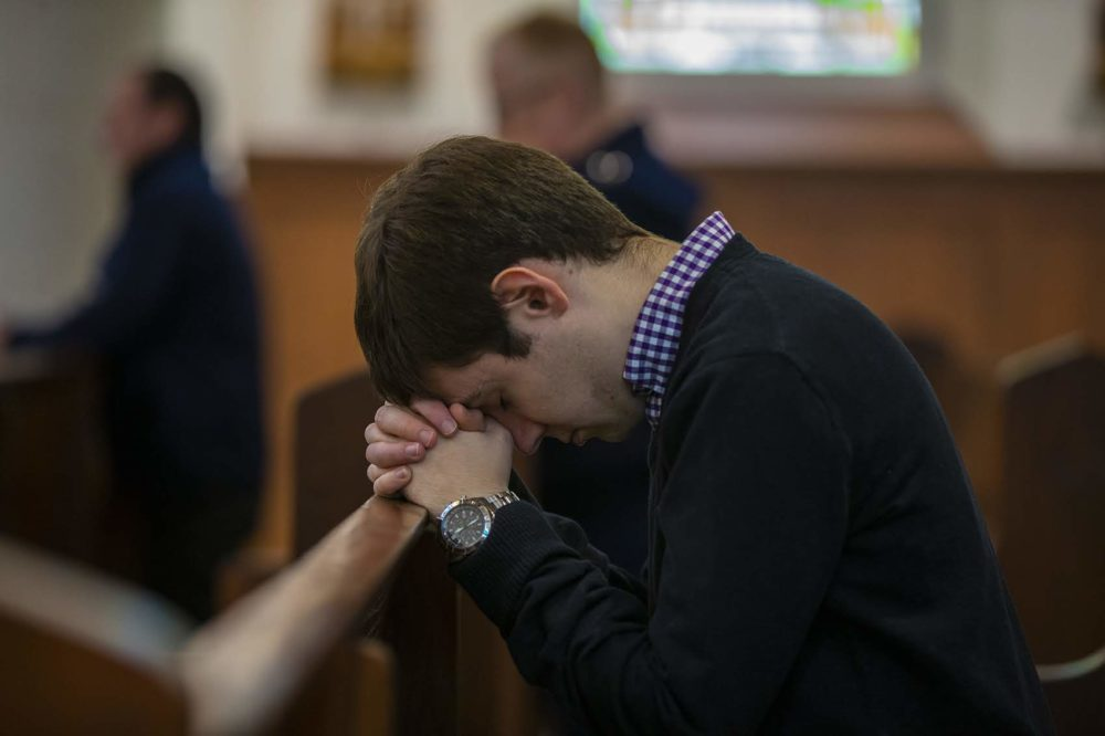 A young man prays in a pew at Shrine of Our Lady of Good Voyage in the Seaport. (Jesse Costa/WBUR)