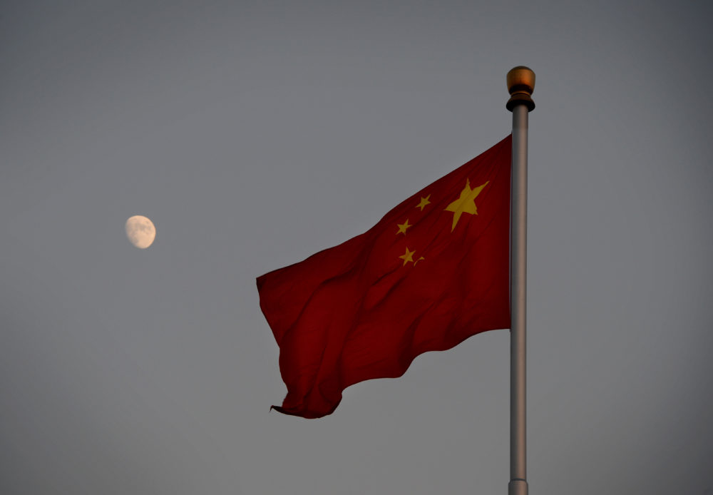 The Chinese flag is seen in front of a view of the moon at Tiananmen Square in Beijing on Dec. 13, 2013. (Mark Ralston/AFP/Getty Images)