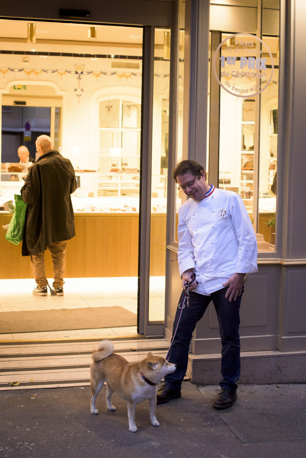 Laurent Duchne, who has been decorated as one of France's top pastry makers, watches a patron's dog, who is named Jacynthe, outside his boutique in the 13th arrondissement on Nov. 12, 2018 in Paris. (Pete Kiehart for Here & Now)