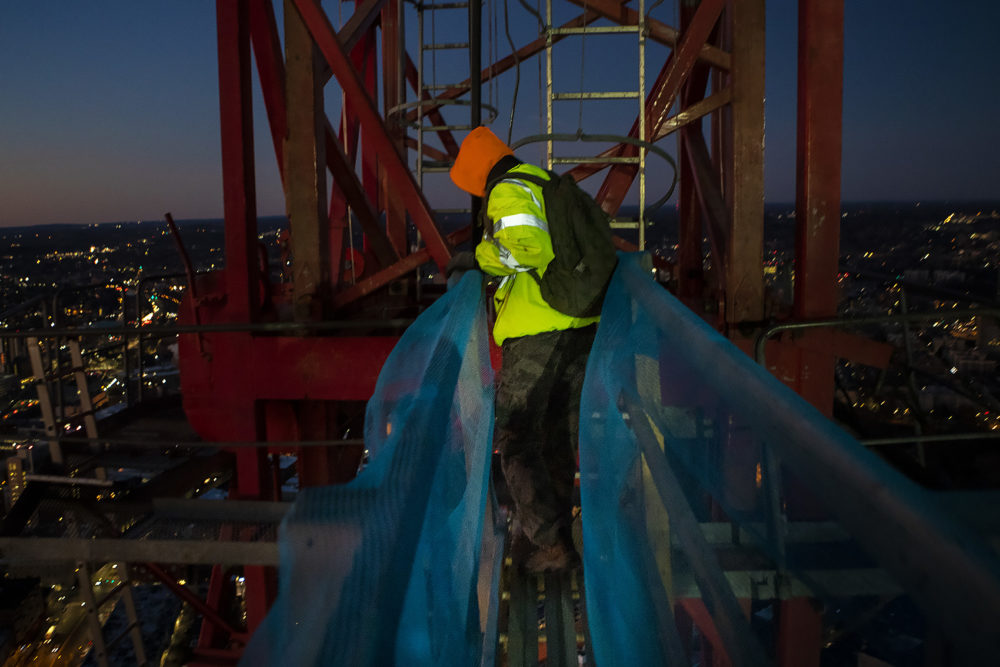 Crane operator Brett St. Germain looks down as he crosses a bridge from One Dalton's 61st floor to the mast of the crane to begin his workday. He'll have to climb five 16-foot ladders before climbing into the crane's cab. (Jesse Costa/WBUR)