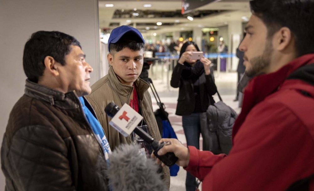 Emerson, 17, and his father, Juan, talk to the press after being reunited at Logan Airport. (Robin Lubbock/WBUR)