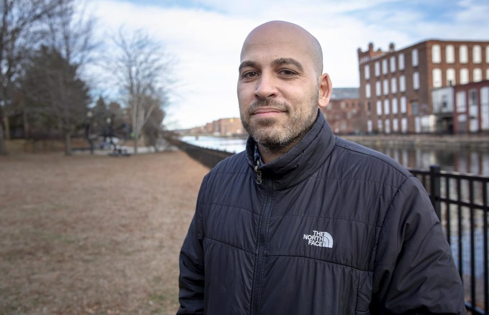 José Bou, who's the equity family and community partnerships manager with Holyoke Public Schools, stands by a canal in the western Massachusetts city. (Robin Lubbock/WBUR)