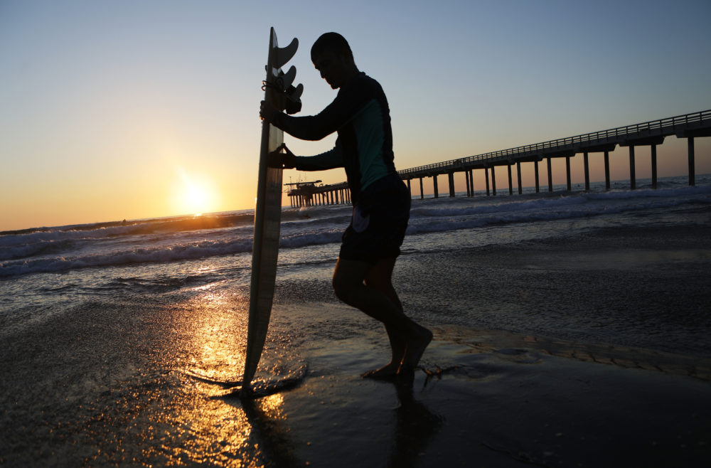 A surfer stands in front of Scripps Pier on the Pacific Ocean on Aug. 7, 2018 in San Diego, Calif. The sea surface temperature at Scripps Pier was measured at an all-time high of 78.8 degrees on Aug. 3, the warmest since record keeping began at the pier 102 years ago. (Mario Tama/Getty Images)