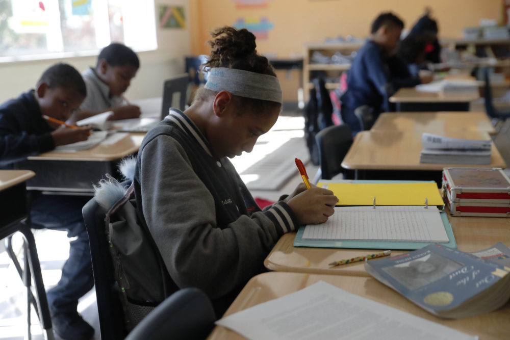 In this Tuesday, Dec. 18, 2018 photo, Breanna Johnson works on her assignment in her 6th-grade English class at Alice M. Harte Charter School in New Orleans. Charter schools, which are publicly funded and privately operated, are often located in urban areas with large back populations, intended as alternatives to struggling city schools. (Gerald Herbert/AP)