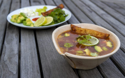 Sopa di lima, Mexican lime chicken soup with tortillas with garnishes in the background. (Jesse Costa/WBUR)