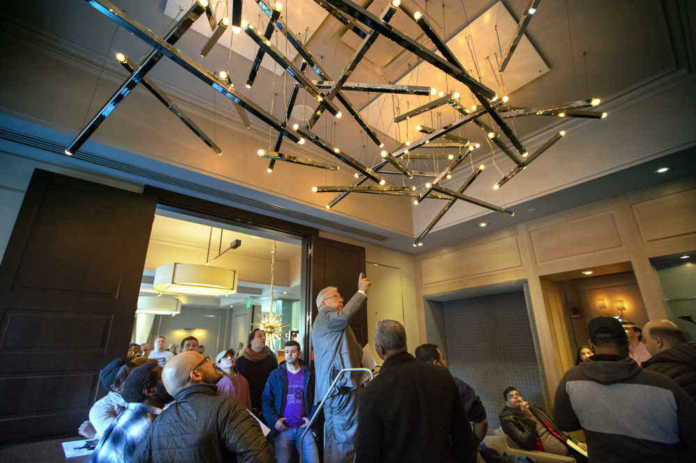 Auctioneer Ed Smith points up to the large chandelier in the entrance of L'Espalier Restaurant to begin the bidding by participants. (Jesse Costa/WBUR)