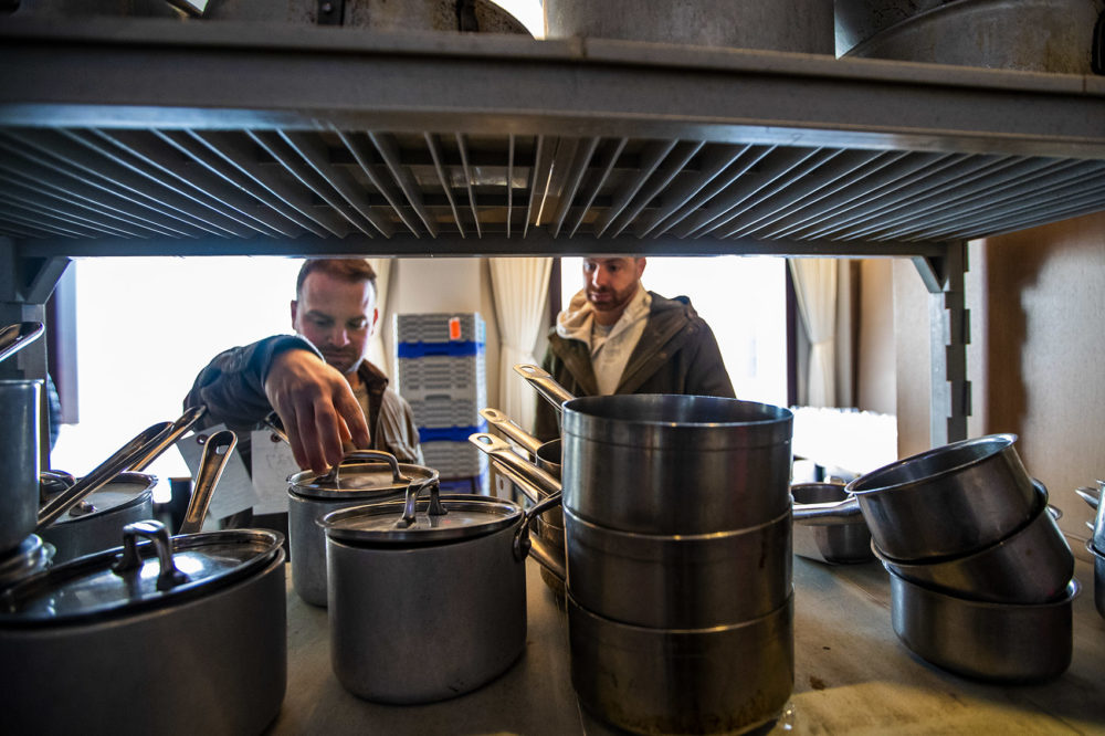 Chris and Jared Palladino of Willy's Ale Room in Acton, Maine, check out some saucepans on a shelf. (Jesse Costa/WBUR)