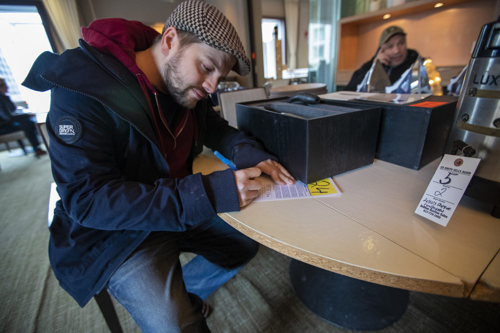 Devon Trevelyan of Knight Moves Cafe in Brookline fills out his auctioneer card before the auction. (Jesse Costa/WBUR)