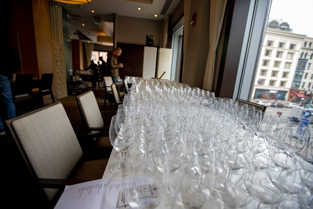 Long tables filled with drink glasses up for bid in the auction. (Jesse Costa/WBUR)