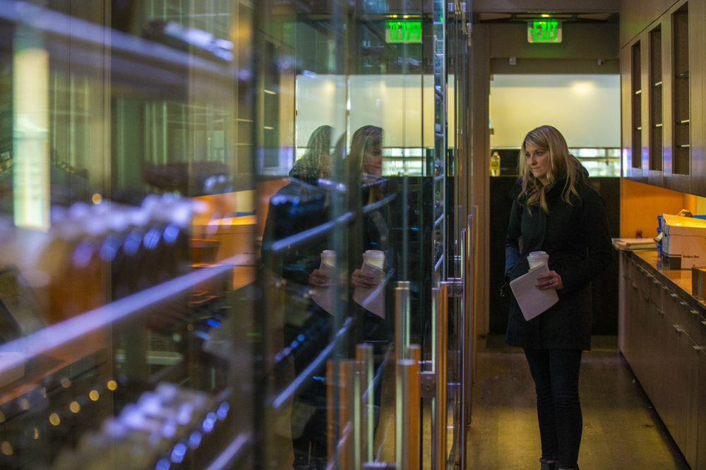 Meaghan Hughes of the restaurant Alchemy in Martha's Vineyard peruses the large case of wine that runs the length of the hallway behind the restaurant. The wine was being auctioned the following day. (Jesse Costa/WBUR)