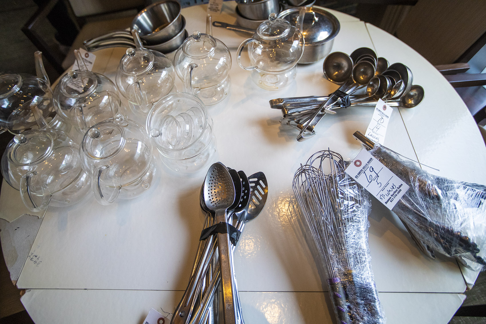 Kitchen utensils and assorted glassware up for auction at the L'Espalier auction. (Jesse Costa/WBUR)