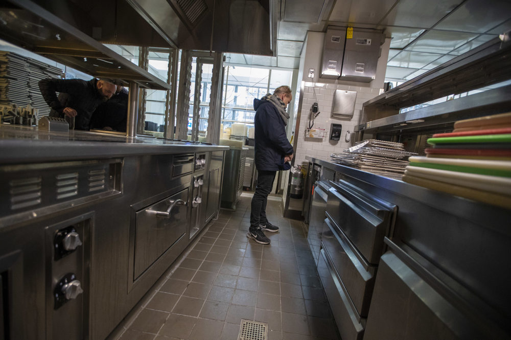 A man checking out the refrigerator cabinet at the L'Espalier auction. (Jesse Costa/WBUR)