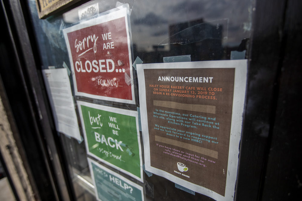 A sign on the front door of the Haley House in Dudley Square in Roxbury explains it closed its retail operation during a re-envisioning process. Meanwhile, the non-profit's catering and wholesale operations will continue. (Jesse Costa/WBUR)