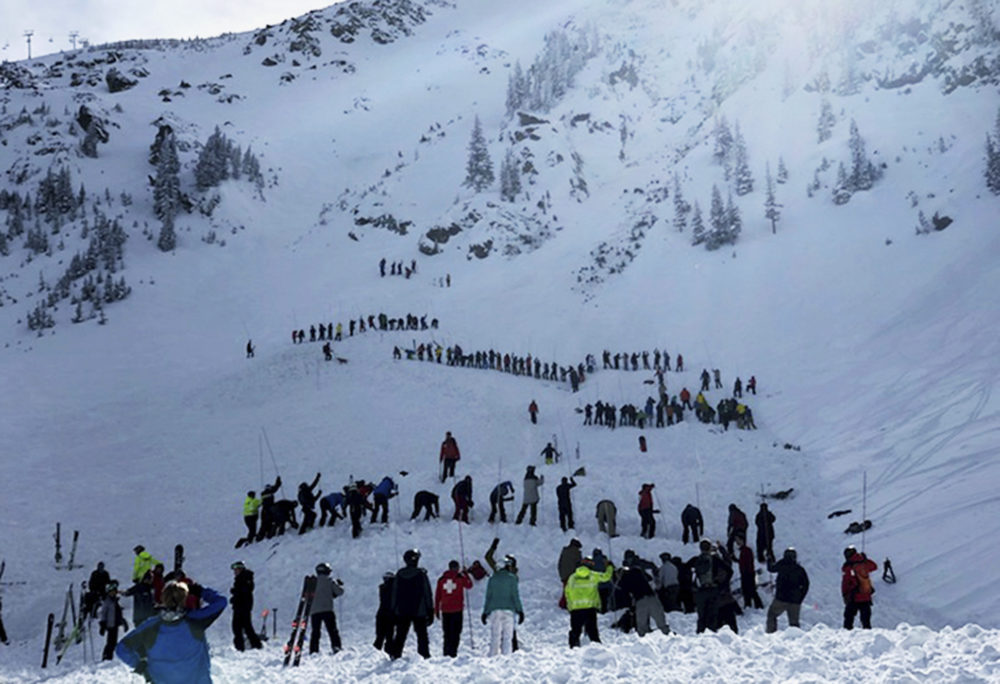 People search for victims after an avalanche buried multiple people near the highest peak of Taos Ski Valley, one of the biggest resorts in New Mexico, on Jan. 17. The avalanche rushed down the mountainside of the New Mexico ski resort on Thursday, injuring at least a few people who were pulled from the snow after a roughly 20-minute rescue effort, a resort spokesman said. (Morgan Timms/Taos News via AP)