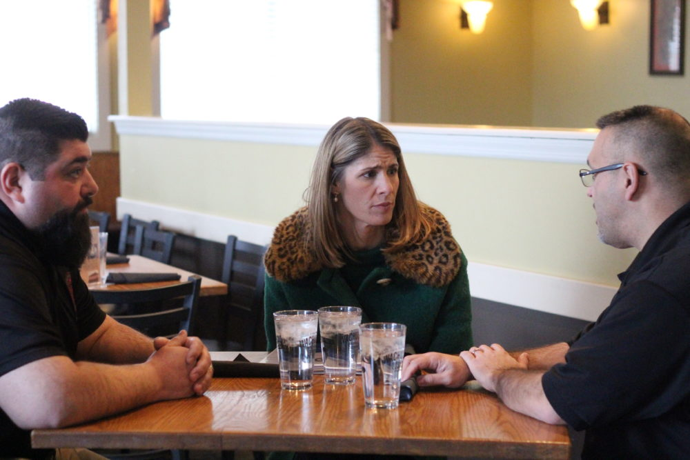 Congresswoman Lori Trahan speaks with two prison officers from FMC Devens. To her left is Jason Basil, and on her right is David Martinez. (Quincy Walters/WBUR)