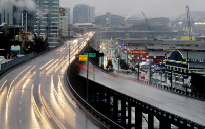 In this long-exposure photo taken Thursday, Jan. 3, 2019, headlights and taillights of Alaskan Way Viaduct traffic lines the highway ahead of an upcoming closure of the roadway, as the city's sports stadiums are seen in the distance, in Seattle. The double-decker highway along Seattle's waterfront was shut down for good Friday, Jan. 11, ushering in what officials say will be one of the most painful traffic periods in the city's history. (Elaine Thompson/AP)
