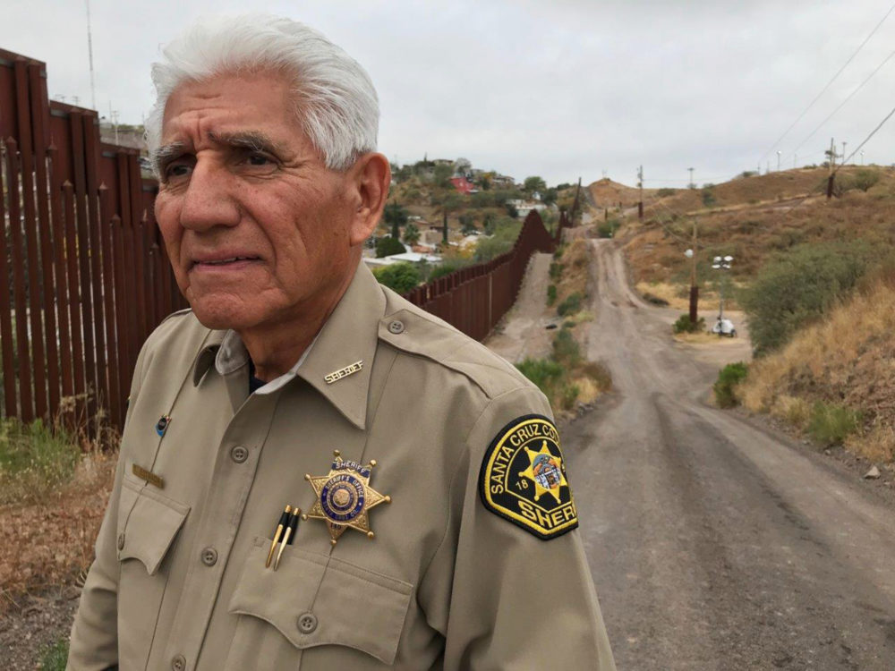 "In this Dec. 5, 2017, photo, Santa Cruz County Sheriff Tony Estrada poses for a photo in Nogales, Ariz., on the U.S. side of the international boundary with Nogales, Mexico, where he was born. Estrada is a critic of President Trump's immigration policies and plans for a ""big, beautiful"" border wall. (Anita Snow/AP)"
