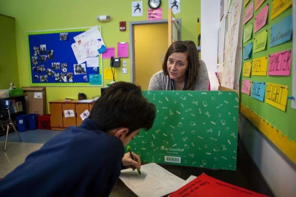 "Boston Collegiate Charter School teacher Bridget Adam plays a math game based on ""Battleship"" with one of her sixth grade students. (JesseCosta/WBUR)"