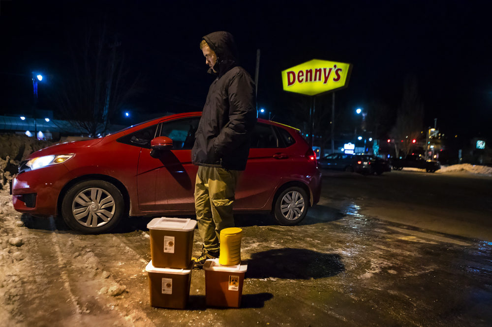 In a Denny's parking lot in Auburn, Maine, Church of Safe Injection founder Jesse Harvey stands behind four containers filled with used needles collected from drug users around Lewiston throughout the evening. (Jesse Costa/WBUR)