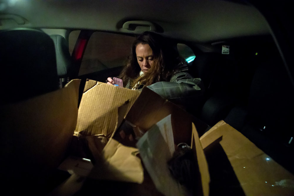 In the backseat of a car, Church of Safe Injection volunteer Kandice Child pulls out a pack of sterile water as she rummages through a box of drug injection-related paraphernalia during a stop at a house in Lewiston, Maine. (Jesse Costa/WBUR)
