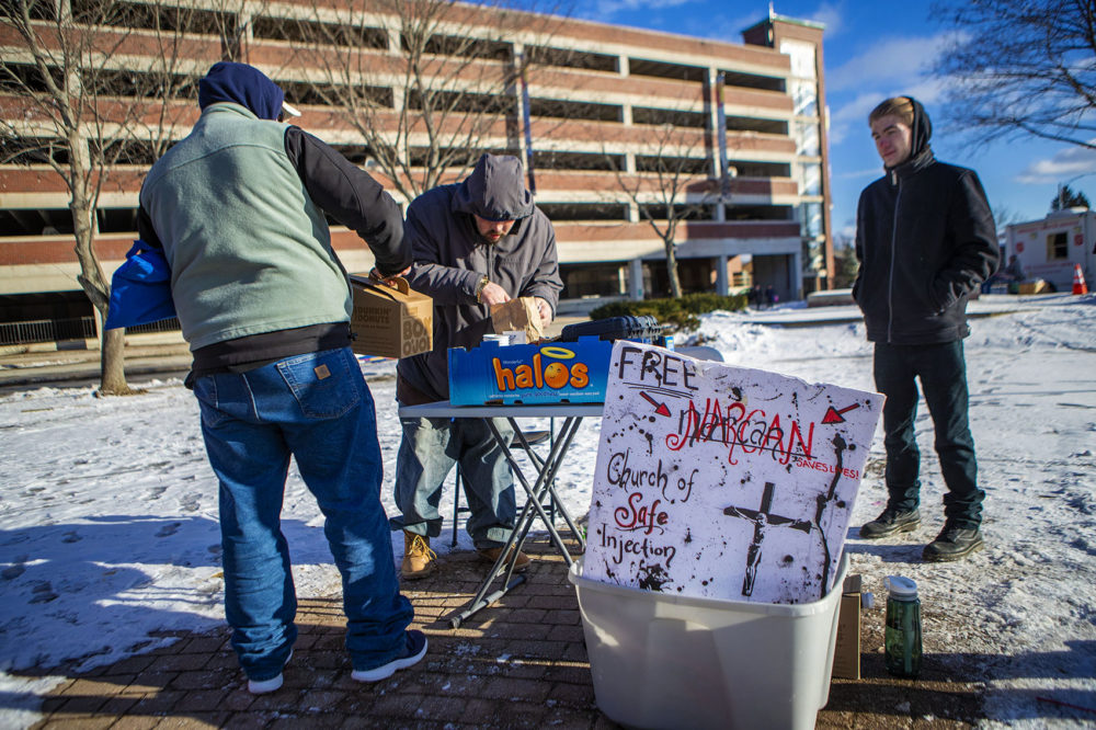 On a frigid 17º F afternoon in Pickering Square in Bangor, Maine, two men stop by a folding table set up by The Church of Safe Injection for some coffee. (Jesse Costa/WBUR)