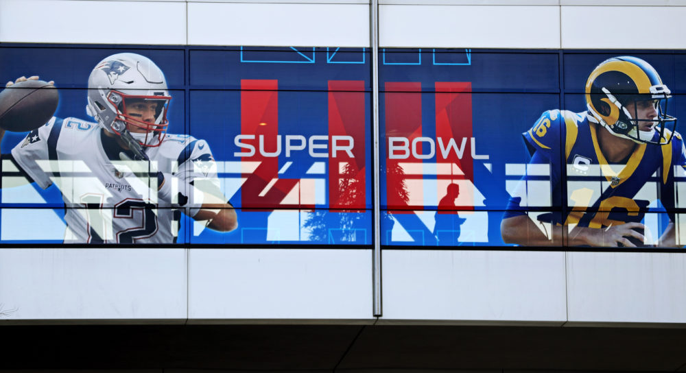 A pedestrian crosses a footbridge decorated with a banner ahead of Sunday's NFL Super Bowl 53 football game between the Los Angeles Rams and New England Patriots in Atlanta on Jan. 30, 2019. (David Goldman/AP)