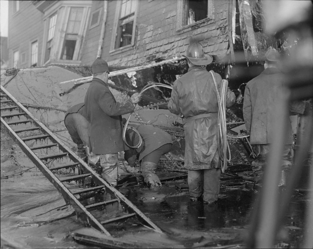 Firemen stand in thick molasses after the Boston molasses flood. (Courtesy of the Boston Public Library, Leslie Jones Collection)