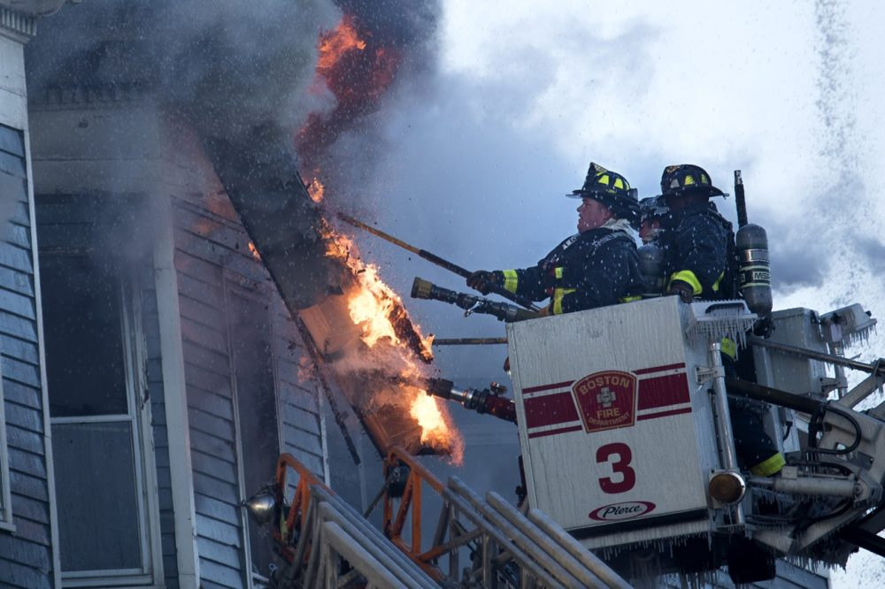 Boston firefighters pull down spme siding to uncover flames to extinguish at a fire at 142-144 Bunker Hill St in Charlestown. (Jesse Costa/WBUR)