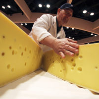 Americans are eating more cheese now than ever before: The country consumed around 37 pounds per capita in 2017. But it's not enough to make a dent in the U.S.' 1.4 billion-pound cheese surplus. Pictured: A volunteer opens a round of Swiss cheese during the World Championship Cheese Contest, March 6, 2018, in Madison, Wis. (Carrie Antlfinger/AP)