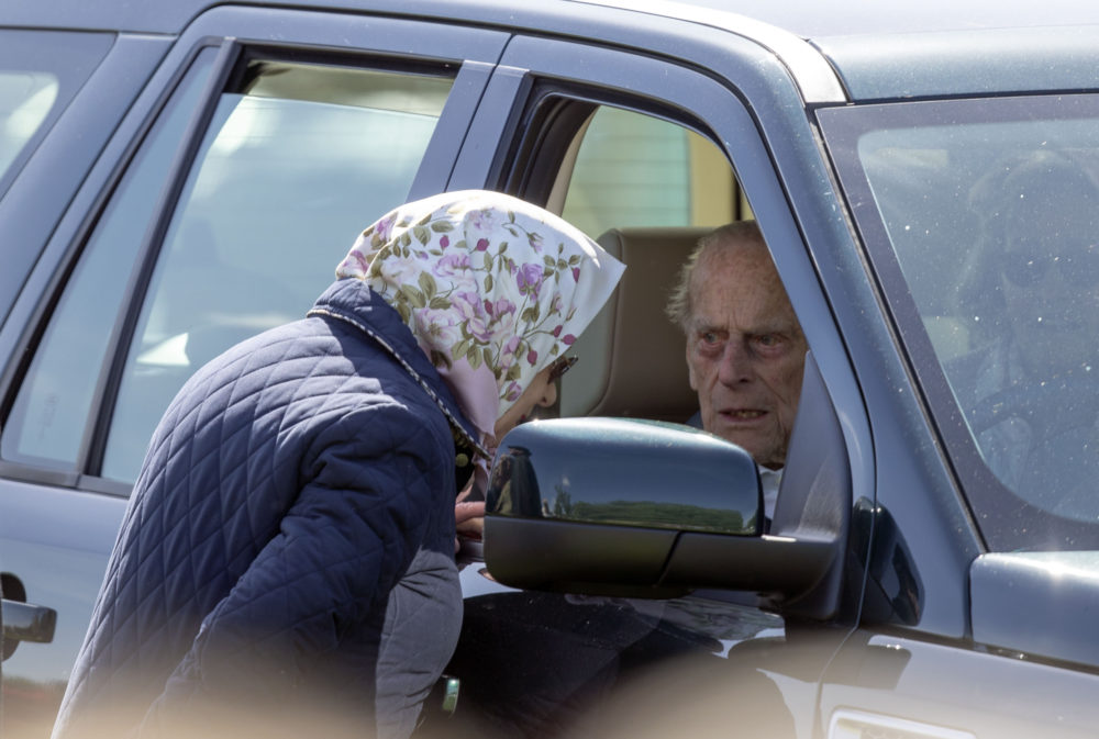 Britain's Prince Philip sits in the driving seat of a car, talking to Queen Elizabeth II during the Royal Windsor Horse Show in Windsor, England, Friday May 11, 2018. (Steve Parsons/PA via AP)