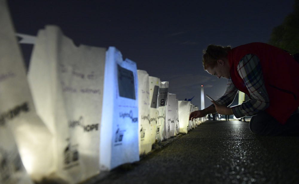 """Dawn Scott of Cody, Wyo., a 20-year cancer survivor, photographs lighted bags in memory of friends and family who died of cancer during a """"Lights of HOPE"""" ceremony in Washington, Tuesday, Sept. 25, 2018. (Susan Walsh/AP)"""