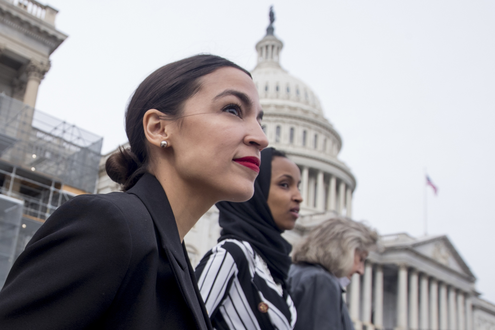 Rep. Alexandria Ocasio-Cortez, left, and D-N.Y., Rep. Ilhan Omar, D-Minn., center, walk down the House steps to take a group photograph of the House Democratic women members of the 116th Congress on the East Front Capitol Plaza on Capitol Hill in Washington, Friday, Jan. 4, 2019, as the 116th Congress begins. Also pictured is Rep. Dina Titus, D-Nev., right. (Andrew Harnik/AP)