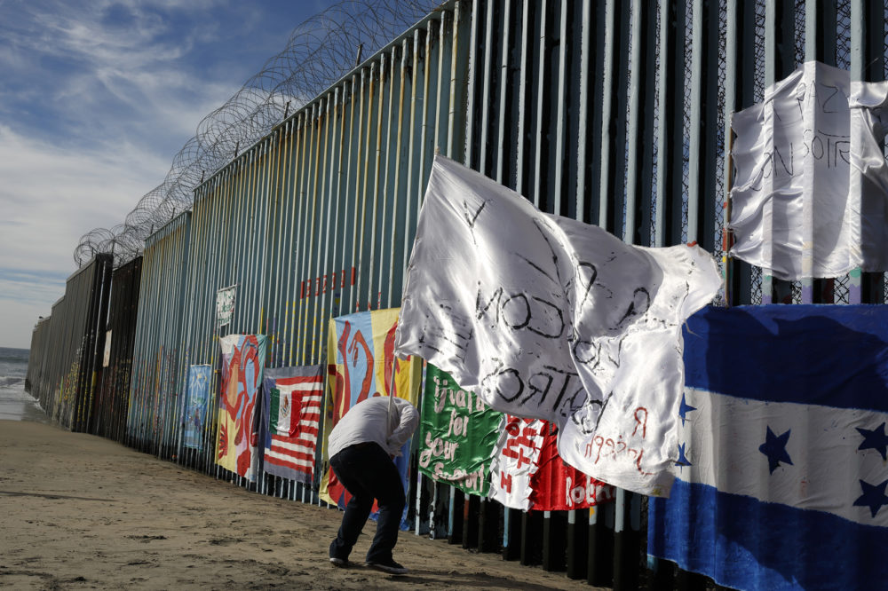 "Joseph, an migrant from Honduras, plants a white flag with the words, ""peace and God with us,"" in front of the border wall during an art display on the border wall, topped with razor wire, Tuesday, Jan. 8, 2019, on the beach in Tijuana, Mexico. (Gregory Bull/AP)"