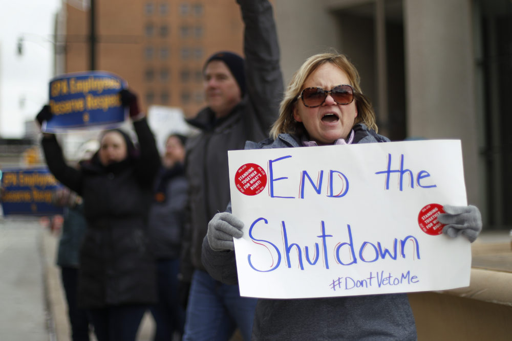 Echo Hunt holds a sign during a rally to call for an end to the partial government shutdown, in Detroit, Thursday, Jan. 10, 2019. (Paul Sancya/AP)
