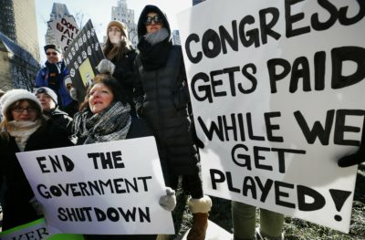 Government workers and their supporters hold signs during a protest in Boston Friday. The workers rallied with Democratic U.S. Sen. Ed Markey and other supporters to urge that the Republican president put an end to the shutdown so they can get back to work. (Michael Dwyer/AP)
