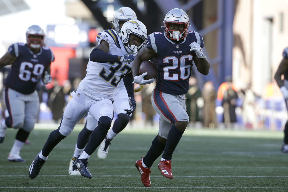 New England Patriots running back Sony Michel (26) runs away from Los Angeles Chargers free safety Derwin James (33) during the first half of an NFL divisional playoff football game, Sunday, Jan. 13, 2019, in Foxborough, Mass. (Steven Senne/AP)