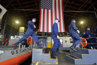 U.S. Coast Guardsmen and women, who missed their first paycheck a day earlier during the partial government shutdown, walk between 45-foot response boats during their shift at Sector Puget Sound base Wednesday, Jan. 16, 2019, in Seattle. (Elaine Thompson/AP)