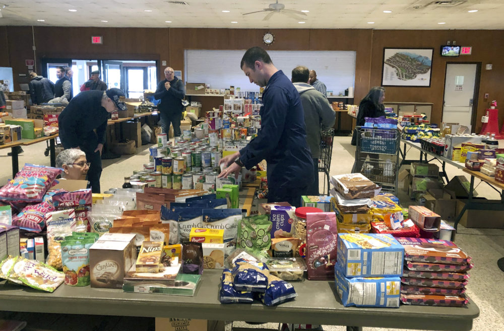 In this Thursday, Jan. 17, 2019 photo, a member of the U.S. Coast Guard arranges donated canned goods at a pop-up food pantry at the U.S. Coast Guard Academy in New London, Conn., that was set up by several Coast Guard-related advocacy groups. (Susan Haigh/AP)