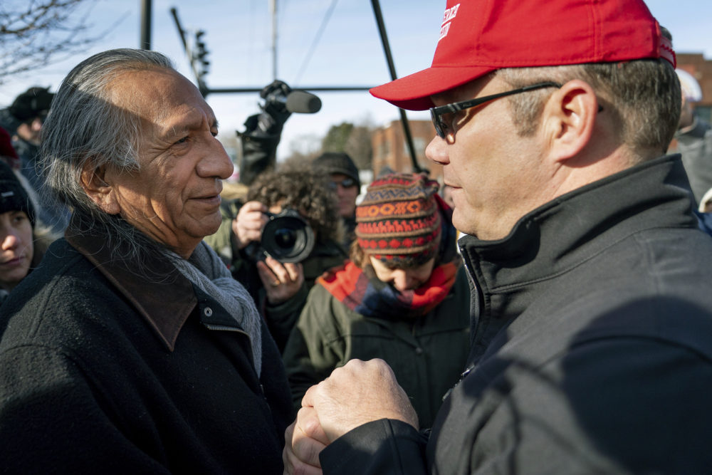 Guy Jones, left, and a supporter of President Donald Trump named Don join hands during a gathering of Native American supporters in front of the Catholic Diocese of Covington in Covington, Ky., Tuesday, Jan. 22, 2019. Jones organized Tuesday's gathering. (Bryan Woolston/AP)