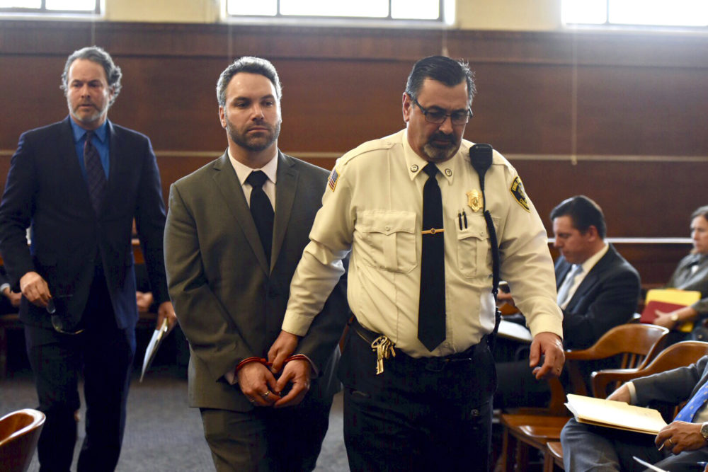 Mark Fitzgerald, of Ashland, Mass., is led by a district court officer Monday in Waltham, where he was arraigned on charges including assault with a dangerous weapon. (Faith Ninivaggi/MediaNews Group/Boston Herald via AP, Pool)