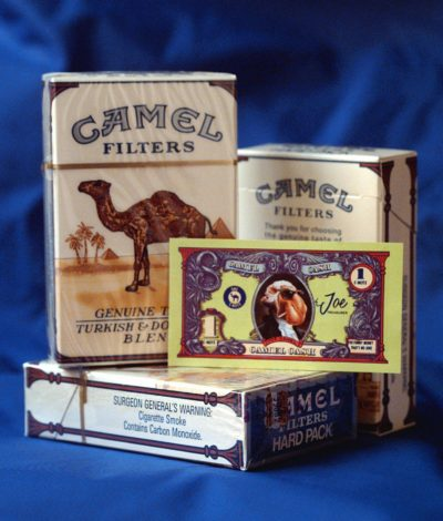 """Packs of Camel cigarettes and a """"Camel cash"""" coupon are displayed in 1997. Joe Camel, the jazzy cartoon character blamed for luring kids into smoking, was retired the same year. (Richard Drew/AP)"""