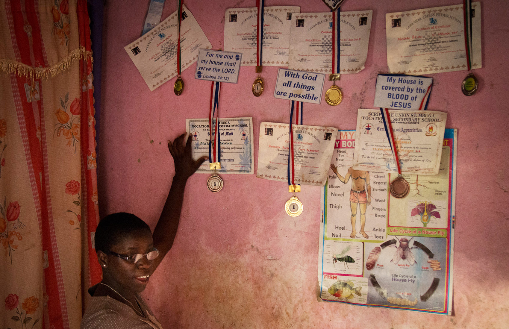 Phiona Mutesi poses with her wall of chess accolades. (Michele Sibiloni/AFP/Getty Images)