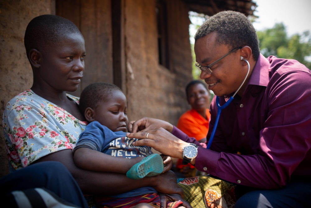 Dr. Dimitri Suffrin checks on HIV and malnutrition patient Agnes Makunda, 3, on September 28, 2018, while she is held by her mother, Margaret. Margaret walks to Ligowe Health Centre in Dzomodya Village, Malawi, at night and sleeps there, outside, with her four children; they are essentially homeless. (Courtesy Partners In Health)