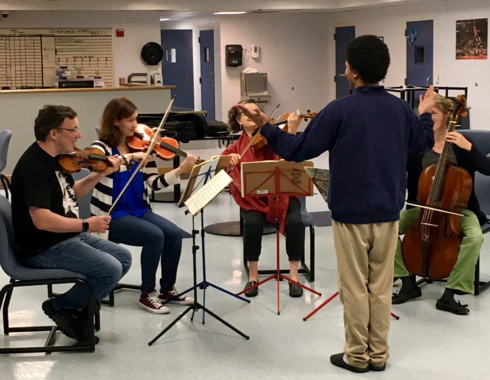 A teen at a Youth Services center tries to conduct musicians from the Sarasa Chamber Music Ensemble. (Courtesy Bruce Mendelsohn)